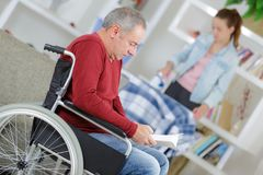 Daughter helping father in wheelchair at home. Man stock image