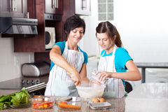 Daughter helping mother baking Royalty Free Stock Photography