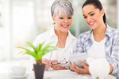 Daughter helping mother calculate. Happy daughter helping middle aged mother calculate her retirement investments Stock Images