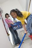 Daughter Helping Mother In Cleaning Floor. Portrait of daughter helping mother in cleaning floor Stock Photography