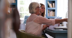 Daughter Helping Senior Mother With Paperwork In Home Office. Adult daughter helping mother to fill in form before she adds her signature. Shot in 4k on Sony stock video footage