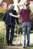 Daughter Helping Senior Mother To Use Walking Frame Royalty Free Stock Photo