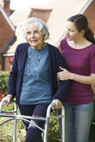 Daughter Helping Senior Mother To Use Walking Frame Stock Photography