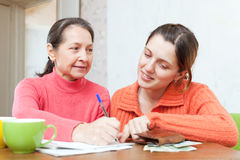 Daughter helps the mother to fills in  utility payments Stock Images