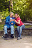 Daughter with her disabled father in wheelchair using a digital Stock Image