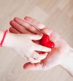 Daughter and her father holding a red heart in their hands Stock Photography