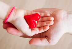 Daughter and her father holding a red heart in their hands Stock Images