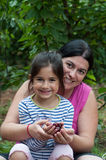 Daughter with her mother collect cherries. Mother and daughter eating cherries stock photography