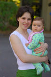 Daughter in her mother's arms. A seven month old baby girl apprehensively frowns in the arms of smiling young mother on a summer day. Selective focus on mother's Royalty Free Stock Photos