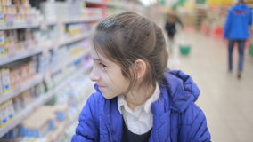 The daughter and her mother are shopping at the supermarket. Little assistant mistress stock video