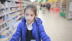 The daughter and her mother are shopping at the supermarket. Little assistant mistress stock footage