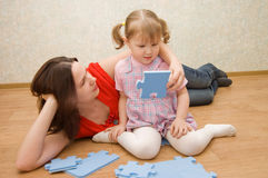 Daughter and her mother are solving puzzle Royalty Free Stock Images