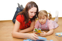 Daughter and her mother are solving puzzle Royalty Free Stock Photo