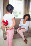 Daughter hiding bouquet of roses for mother on the couch. At home in the living room Stock Photos