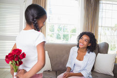Daughter hiding bouquet of roses for mother on the couch Royalty Free Stock Image