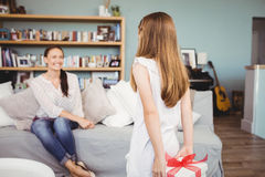 Daughter hiding gift box from mother. Sitting on sofa at home Royalty Free Stock Image