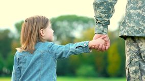 Daughter holding hand of her military father. Little girl in jeands coat with father stock video footage