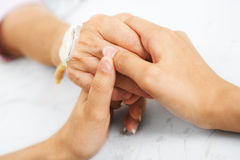 Daughter holding her mother hand in hospital Stock Images