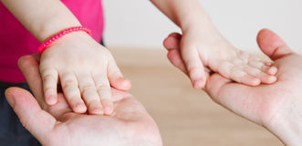 Daughter holding her palms in father's palm's Royalty Free Stock Photos