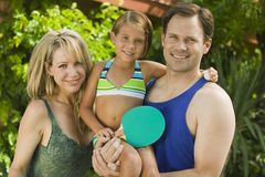 Daughter (7-9) holding ping-pong paddle with parents portrait. Stock Images