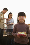 Daughter holding plate with hotdog and salad, parents standing next to the barbeque Stock Images