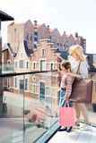 Daughter holding shopping bags while mother pointing somewhere Royalty Free Stock Images