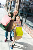 Daughter holding teddy bear while father holding shopping bags and pointing somewhere Stock Photos