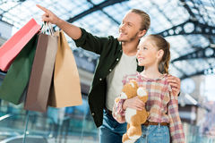 Daughter holding teddy bear while father holding shopping bags and pointing somewhere Royalty Free Stock Image