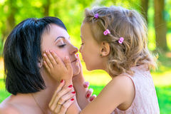 Daughter holds the face of his mother and kisses Stock Image