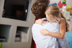 Daughter Hugging Father Returning From Work Stock Photo