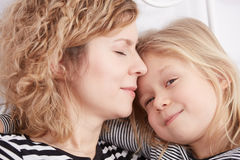 Daughter hugging her mom. Little daughter smiling and hugging her sleeping mom royalty free stock photography
