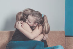Daughter hugging his mother at home. Concept of couple family is in sorrow.  Royalty Free Stock Photography