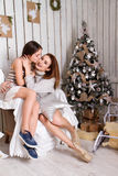 Daughter hugging and kissing her mother near Christmas tree Royalty Free Stock Images