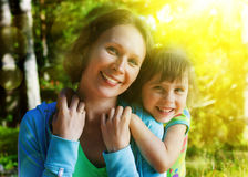 Daughter hugging mother. On a bright sunny day Stock Image