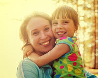 Daughter hugging mother. On a bright sunny day Stock Images