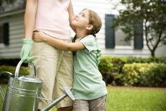 Daughter hugging mother carrying watering can Stock Photos