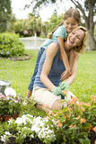 Daughter hugging mother gardening Stock Image