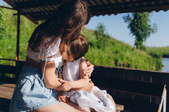 Daughter hugging mother. In the gazebo on a hot summer day. The concept of relaxation and happiness. Toning Royalty Free Stock Photography