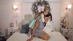 The daughter hugs her pregnant mother on the bed. The daughter hugs her pregnant mother tightly on the bed near the Christmas tree in the Christmas interior stock video footage
