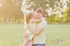 The daughter hugs and kisses her father in the park. Father`s Day stock photos