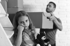 Daughter hugs teddy bear and father puts box into pile. Kid and guy move in or move out. New home. Loneliness and family concept. Girl with sad face and busy stock photos