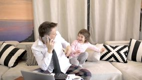 Daughter interrupts her father`s business call stock footage