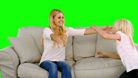 Daughter jumping in the arms of her mother on green screen