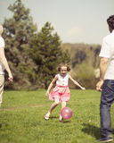 Daughter kicking ball to father and mother in park Royalty Free Stock Images