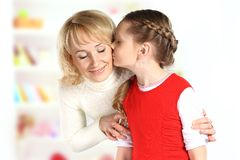 Daughter kiss her mother Stock Photography
