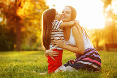 Daughter kiss mother. Daughter kiss her mother on the cheek. Family sits on a green lawn in the city park outdoors Royalty Free Stock Image