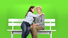 Daughter kisses her mother on the cheek. Green screen