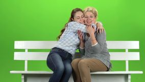 Daughter kisses her mother on the cheek. Green screen. Slow motion. Daughter kisses her mother on the cheek and hugs her, they are sitting on a white bench stock video