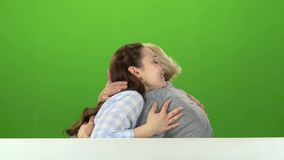 Daughter kisses her mother on the cheek and hugs he. Green screen. Side view. Daughter kisses her mother on the cheek and hugs her, they are sitting on a white stock footage