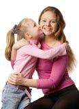 Daughter kisses mum Stock Photos